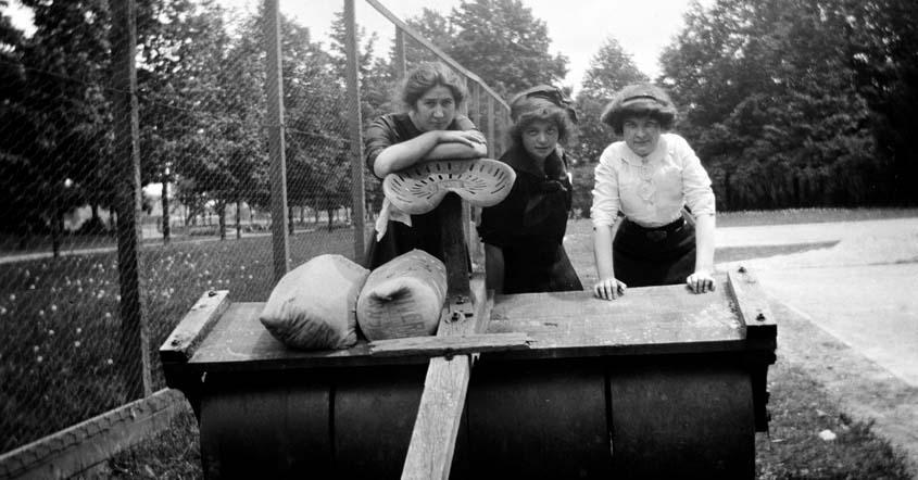 1915 image of three women standing by groundskeeping equipment.jpg