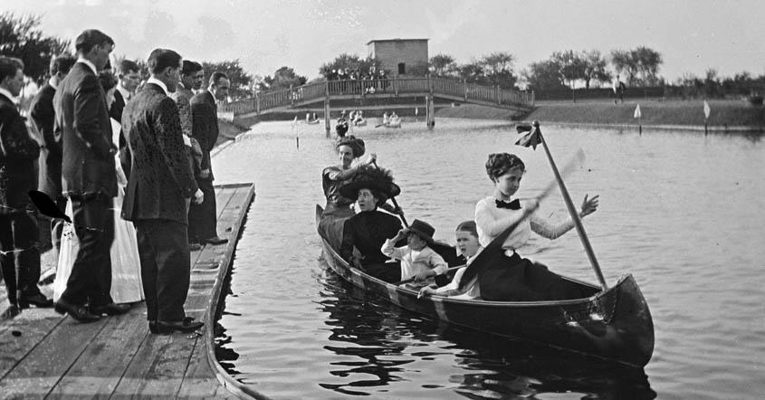 1915 image of women paddling boat in Lake Marian with men standing on dock