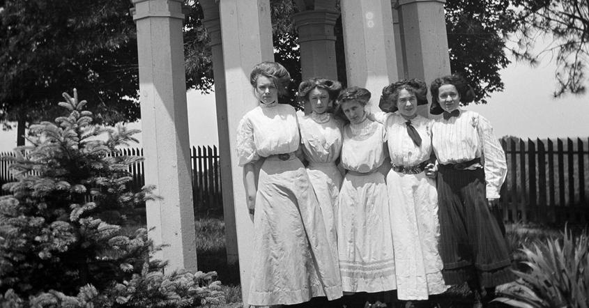 Girls in white dresses standing in group by gazebo