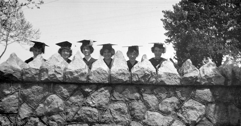 Six graduates in gowns behind stone wall by the Avenue entry