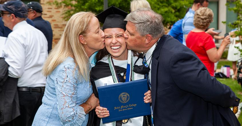 Mom and Dad giving their Graduate a kiss