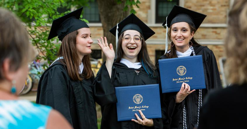 Graduate showing off their diplomas