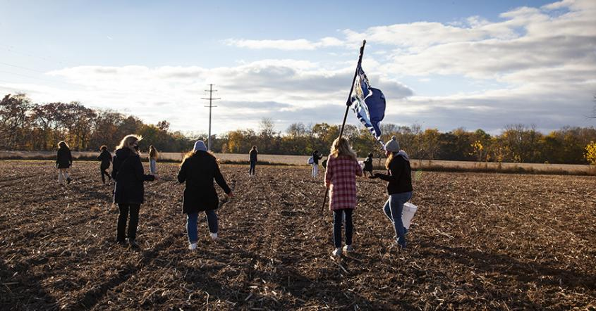 Students and staff sow the seeds of the first planting at the sustainable farm