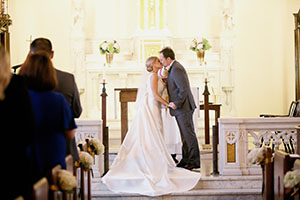 bride and groom kissing in front of the altar
